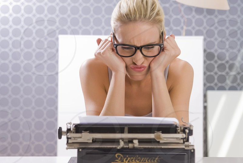 dissatisfied Woman typing on a Antique typewriter photo
