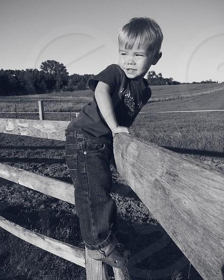 Young boy climbing farmyard fence photo
