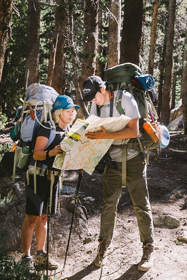 man and woman hikers holding map in middle of the woods photo