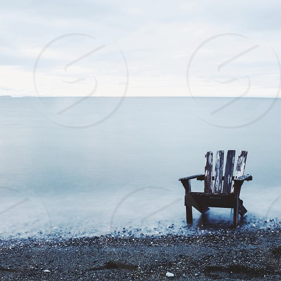 empty brown wooden chair on sea scape photography photo