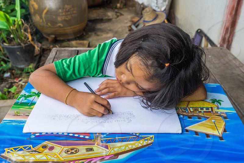 A kid doing school homework. photo