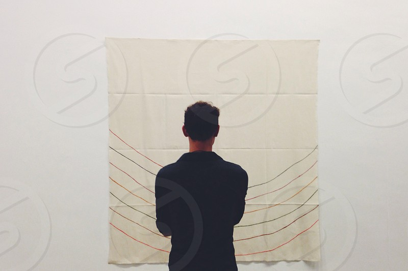 man looking at lines on a white canvas photo