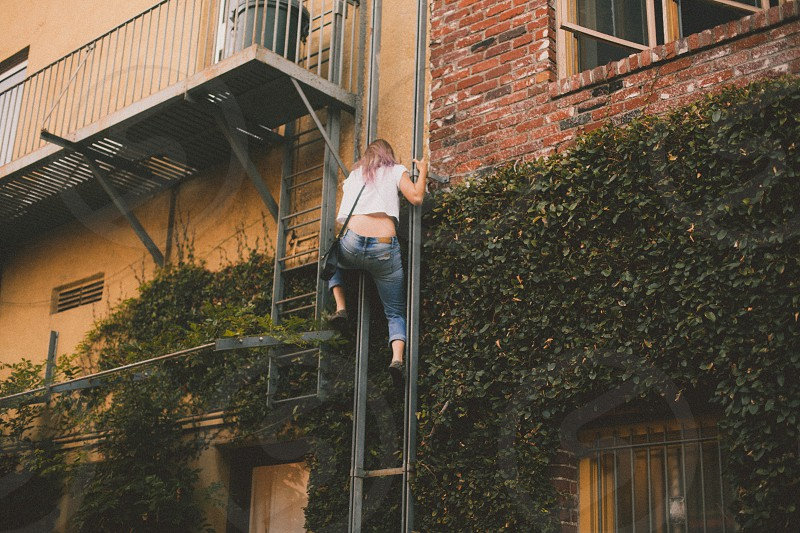 woman climbing up fire exit stairs photo