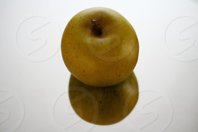 Yellow golden delicious apple reflection on mirror photo