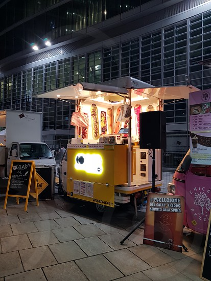 yellow lighted food stall near building photo