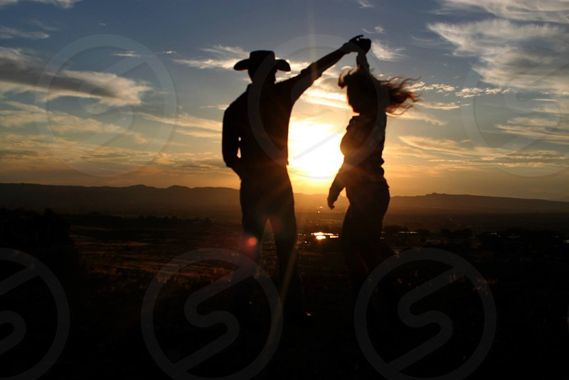 man and woman dancing at hill top during sunset photo