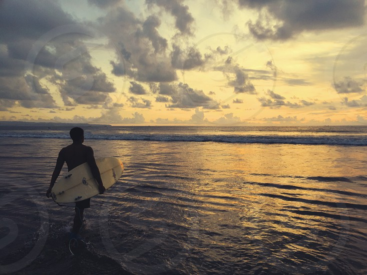 Man beach sea surf sunset water golden golden light Bali island travel trip vacation summer sports leisure recreation  photo