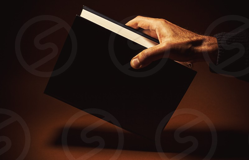 One thick book in a male hand on brown background. Looks like dictionary or an encyclopedia. photo