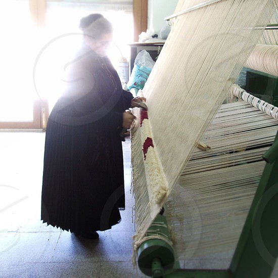 woman in black long sleeved dress standing and weaving photo