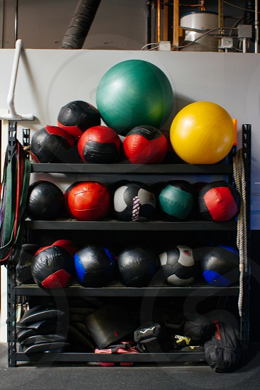 green yellow stability ball and volley ball on black wooden rack photo