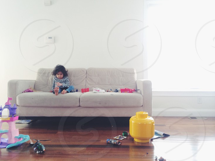 child sitting on top of a white couch photo