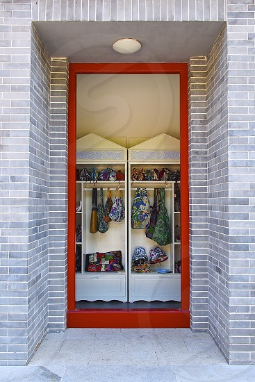Gray bricks and red door. Street side shop. Small business. Colorful products.  photo