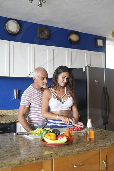 Older man and young woman enjoying cutting vegetables in their kitchen photo