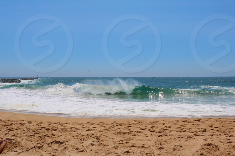 green and blue ocean across beach shore during daytime photo
