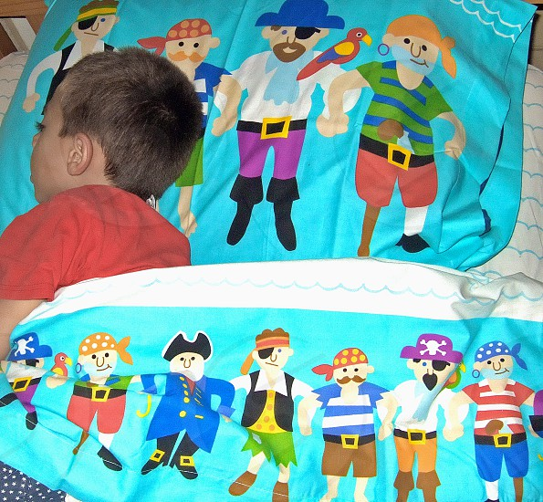 Little Boy sleeping under colorful pirate themed sheets photo