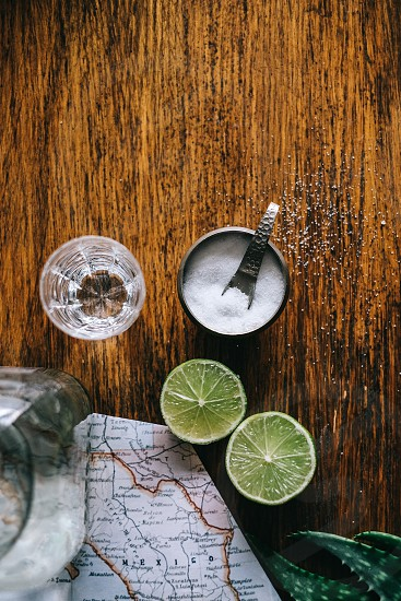 lemon slat and shot glass on brown wooden table photo