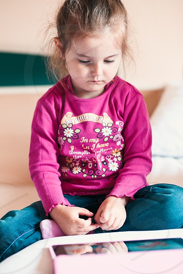 Little girl watching a animated movie for kids on tablet sitting in bed in bedroom photo
