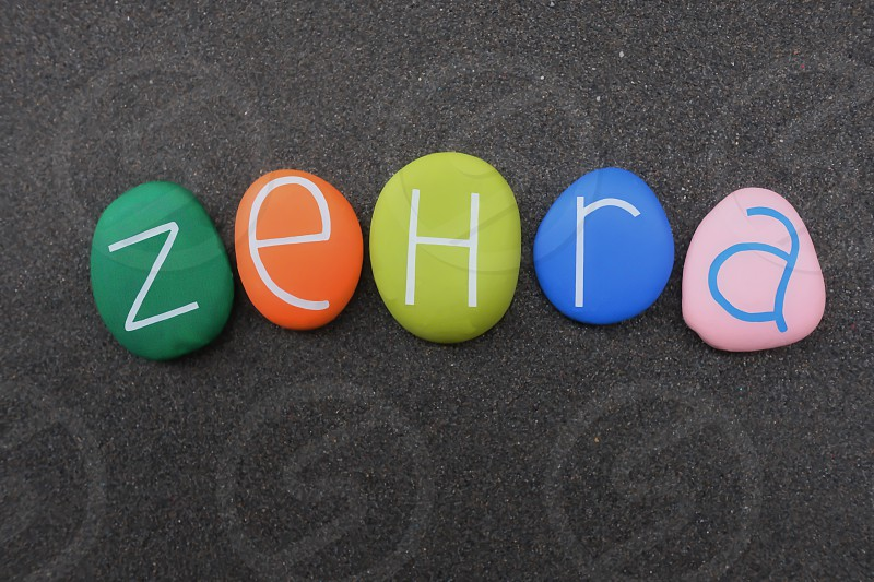 Zehra turkish female name meaning blossoms beauty composed with multi colored stone letters over black volcanic sand photo