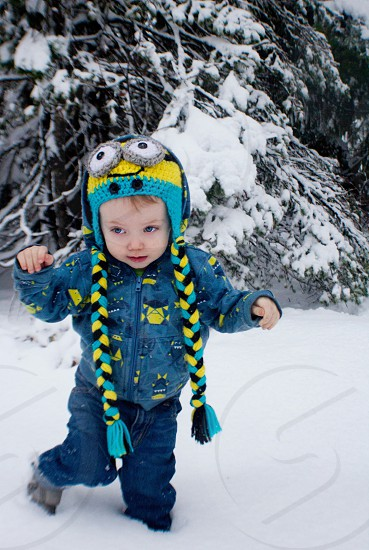 boy wearing blue and yellow minion aviator knit cap on snow photo