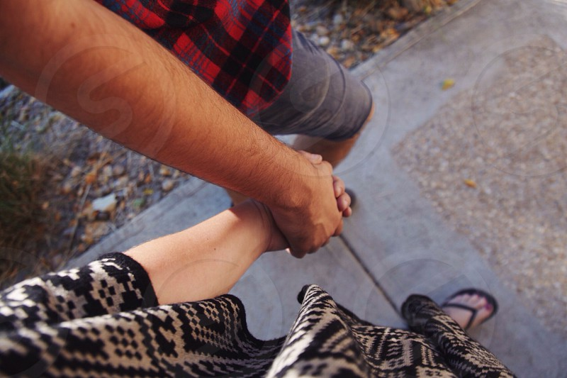couple holding hands while walking on pavement photo