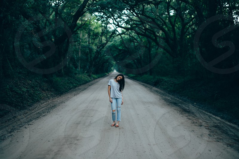 woman in grey shirt blue denim distressed jeans standing on grey road surrounded by green trees photo