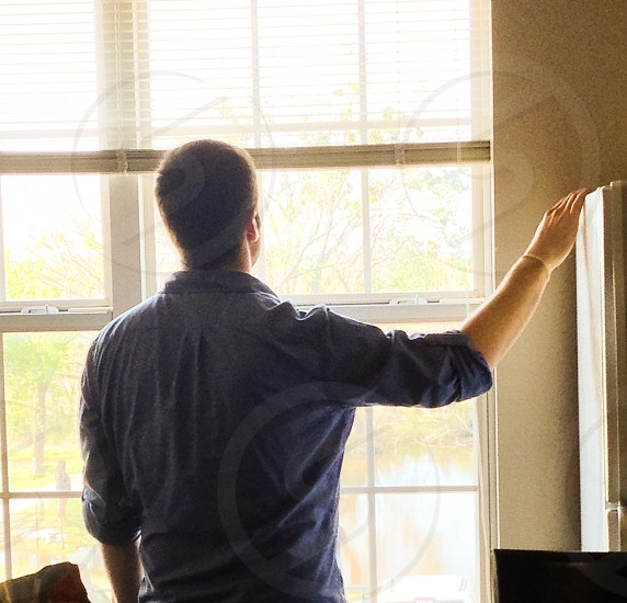 man in blue dress shirt staring outside the window photo