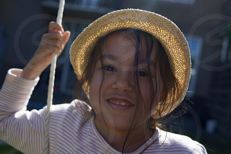 Portrait of a cute Asian girl wearing a straw hat looking happily into camera sitting on a swing in summer sunshine photo