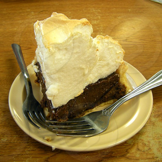 Very tall chocolate meringue pie slice with two forks photo