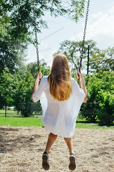 Blonde Girl on Swing with white shirt and black converse. NOTE: Higher resolution version available. photo