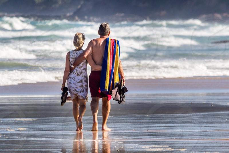Tropical destination couple beach walking photo