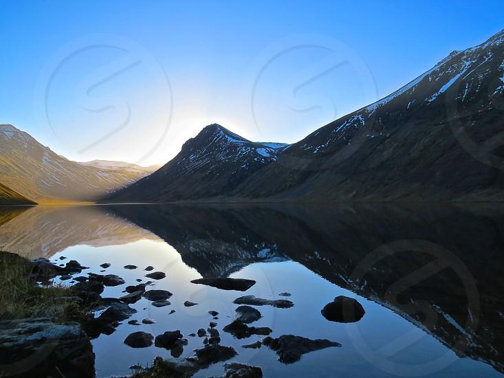reflection of mountain on lake at daytime photo