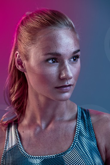 Athletic poses in studio using neon pink and blue lights with female fitness model photo