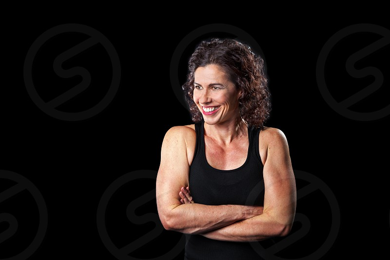 Portrait of a muscular woman smiling and looking off to one side.  Lots of copy space and path around woman.  Black background cross lit. photo