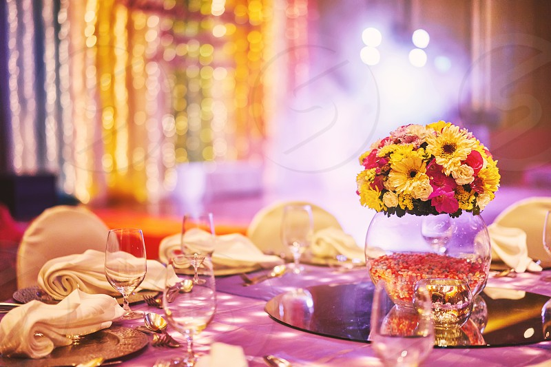 Colorful wedding reception dinner table with flower bouquet decoration in the indian sangeet night with colorful lighting photo