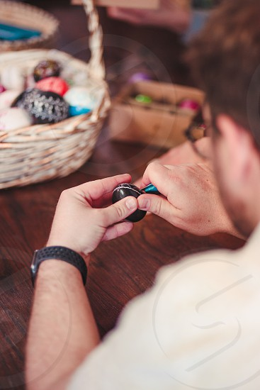 Man decorating the Easter eggs by scratching patterns on dyed eggs. Traditional Easter time spring time new beginnings. Candid people real moments authentic situations photo