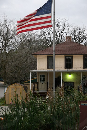 american flag flying on pole in front yard of tan two story house photo