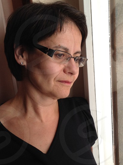 woman in black eyeglasses and shirt leaning near window photo