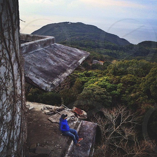 person on edge of overhang and mountains photo