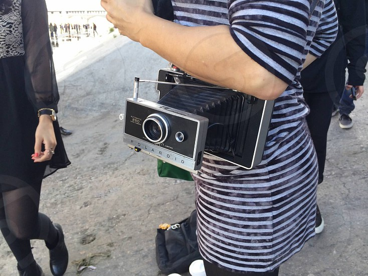woman in black and grey striped dress holding black and grey camera photo