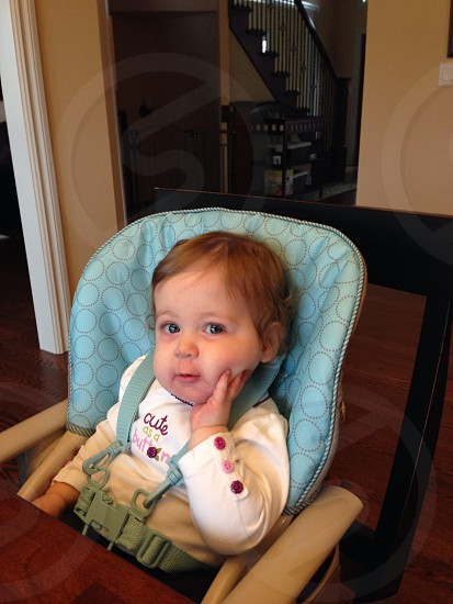 toddler's white long-sleeved shirt sitting on high chair photo
