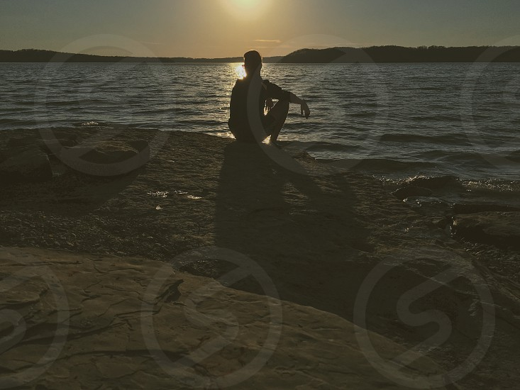 person sitting on brown rock in silhouette figure in front of ocean photo