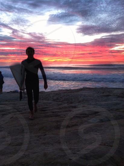 man holding white surfboard on beach photo