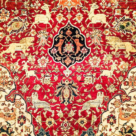 Close up of antique turkish rug with red base and black and gold patterns photo