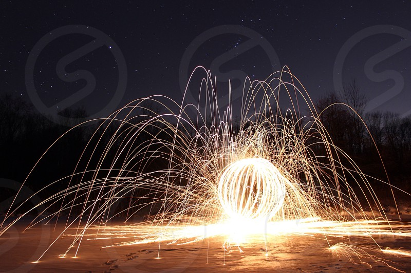 person playing with lighted steel wool during nighttime photo