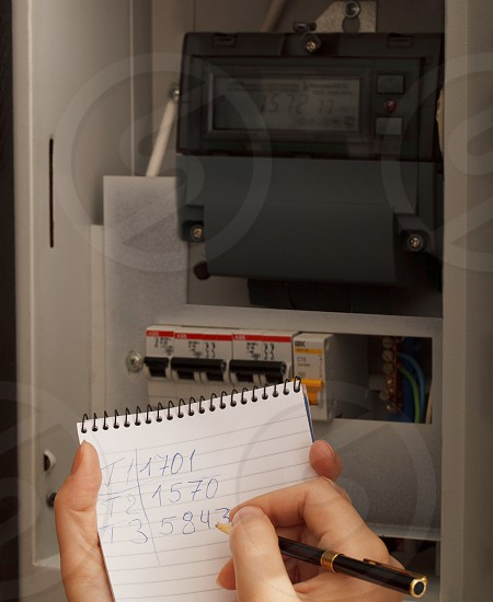 Rewriting of the electrical meter readings at home in Russia. Close up shot. photo
