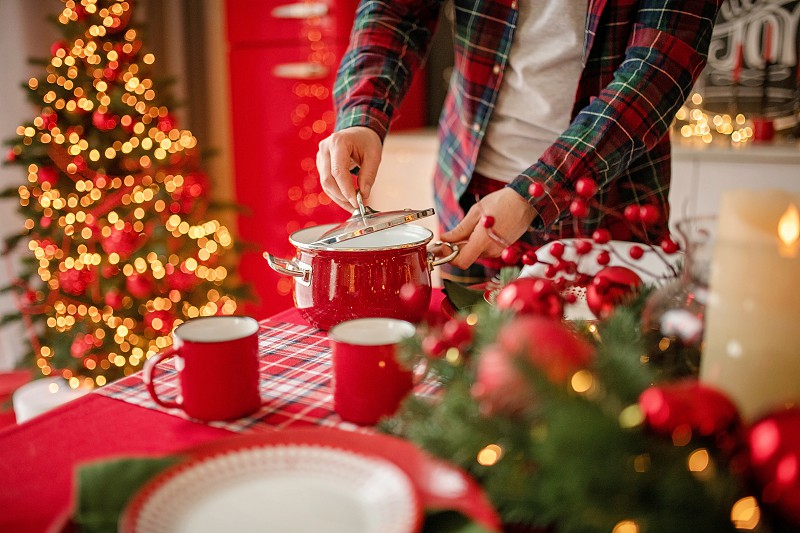 adult man preparing dinner in a festive kitchen decor. Happy New Year and Merry Christmas photo