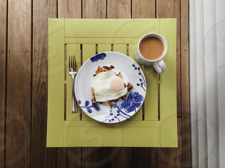 food on top of white and blue floral round ceramic plate between ceramic mug with brown content and stainless steel fork on top of green mat on table photo