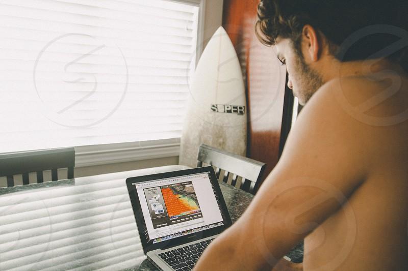 man looking at macbook pro laptop computer photo