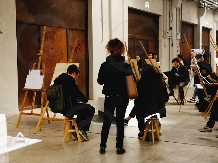 group of people sitting on wooden stool painting on a-frame easel photo