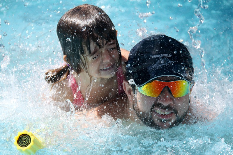 man swimming with daughter photo